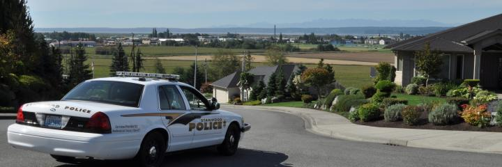 Police cruiser parked overlooking houses and open spaces