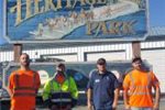 Employees in Front of Heritage Park Sign